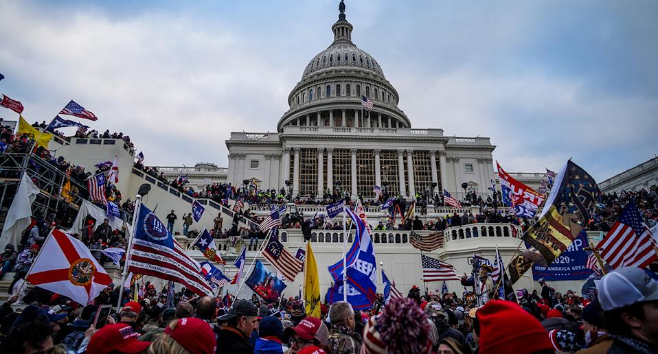 Trump supporters storm the US Capitol holding flags.