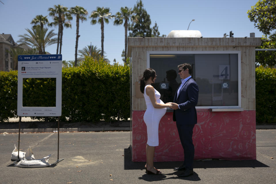 Jeffery Baker and Shannon Carney, who is eight months pregnant, exchange vows during their marriage service in a parking lot in Anaheim, Calif., Tuesday, May 26, 2020. One witness for each couple is allowed while the rest of the wedding guests are asked to stay in their cars. (AP Photo/Jae C. Hong)