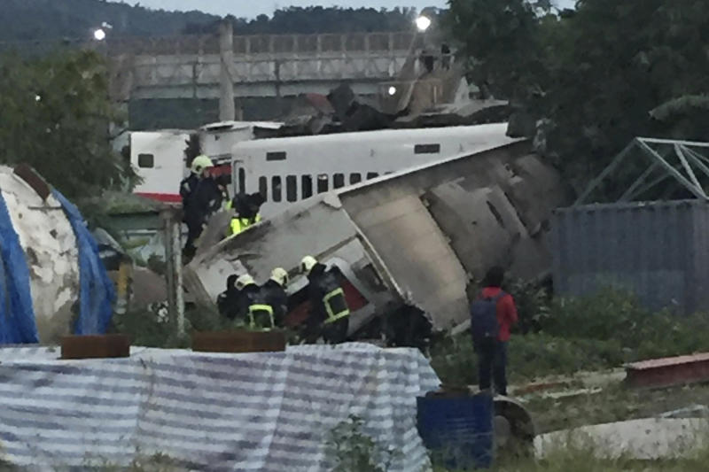CORRECTS PLACE - In this photo released by Li Jun, rescue workers are seen at the site of a train derailment in Yilan county northeastern Taiwan on Sunday, Oct. 21, 2018. The Puyuma express train was carrying more than 300 passengers toward Taitung, a city on Taiwan's southeast coast, when it went off the tracks on Sunday afternoon. (Li Jun via AP)