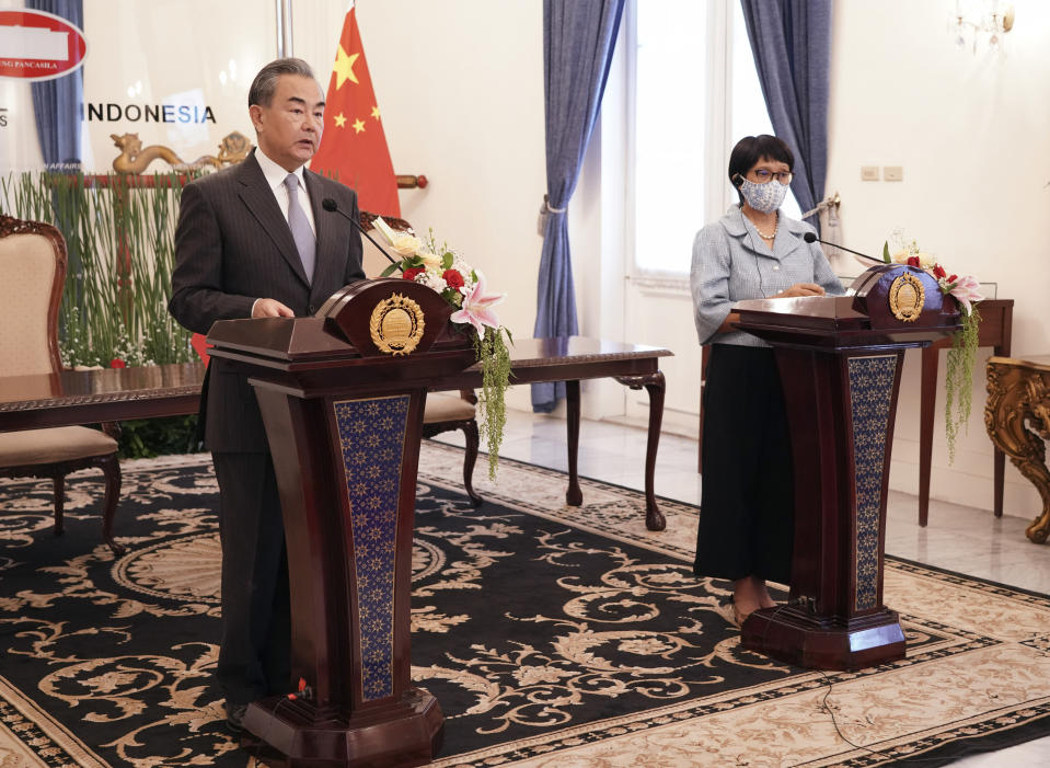 In this photo released by Indonesian Foreign Ministry, Chinese Foreign Minister Wang Yi, left, talks to the media as his Indonesian counterpart Retno Marsudi listens during a virtual press conference following their meeting in Jakarta, Indonesia, Wednesday, Jan. 13, 2021. Wang pledged that China will help Indonesia defeat the coronavirus, including providing vaccines and the strengthen economic cooperation with Indonesia in addition to strengthening cooperation in the health sector in overcoming the COVID-19 pandemic. (Indonesian Foreign Ministry via AP)