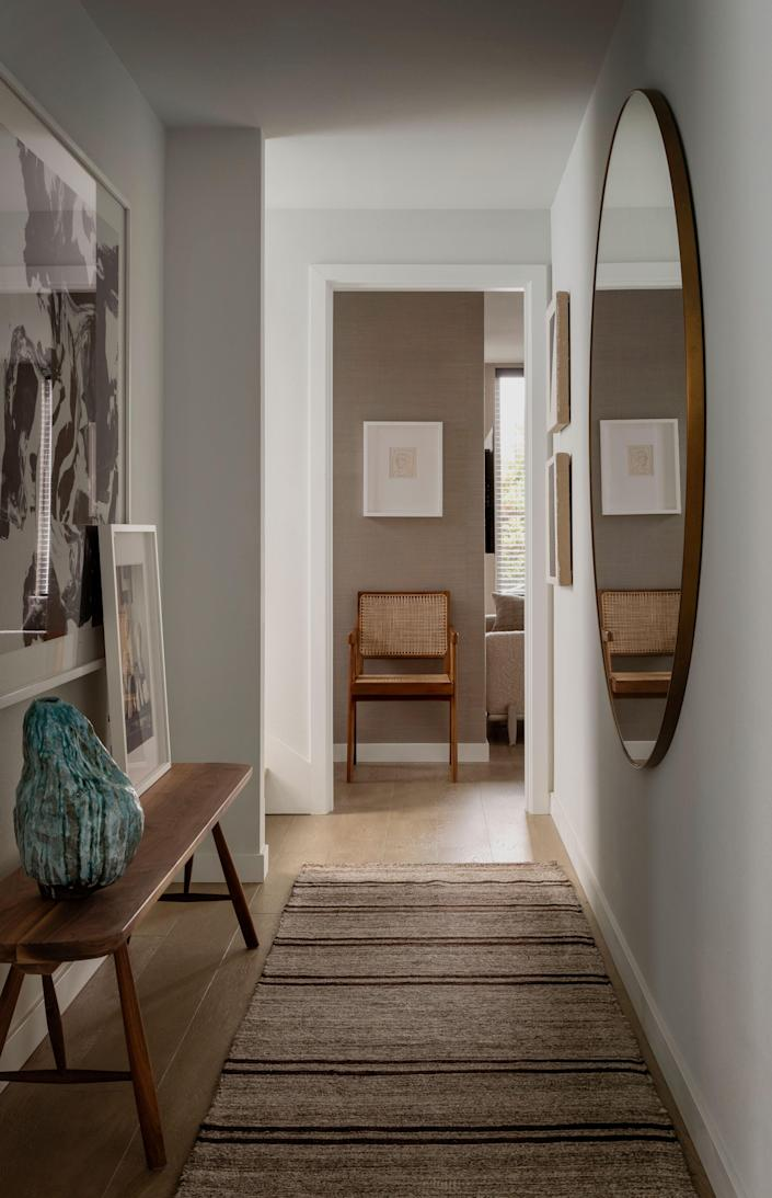 """The hallway on the second floor, which leads from the guest room to the primary bedroom, features a blue ceramic piece by Jojo Corväiá, a Venezuelan artist based in Berlin. """"When I first moved to Seattle, [Corvaia] had a coffee shop here called Cafe Arabica, and it was the best coffee shop,"""" recalls Paquette. """"He was just this amazing person to be around."""""""