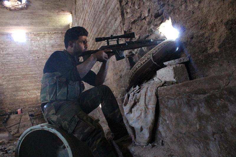 A Syrian rebel aims his rifle from behind a wall as he holds a position on the outskirts of Papoulan, in Idlib province, on April 13, 2014