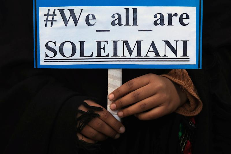 A woman holds a sign with others during a protest over the death of Iranian Major-General Qassem Soleimani, who was killed in an air strike near Baghdad, in Peshawar,