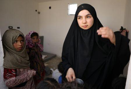 Girls look at Lebanese Nour al-Huda, wife of a former Islamic State fighter, at a camp for displaced people in Ain Issa, north of Raqqa, Syria June 21, 2017. Picture taken June 21, 2017. REUTERS/Rodi Said