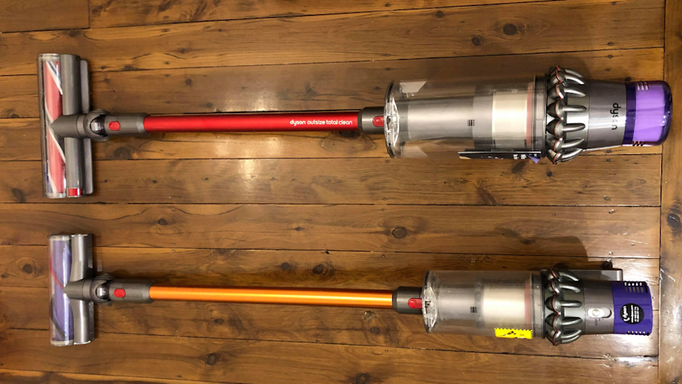 The Dyson Outsize Total Clean stick vacuum laying down next to a Dyson v10 absolute plus stick vacuum to compare the sizes