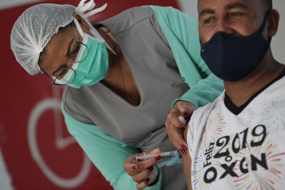 A health worker gives a shot of the Johnson & Johnson COVID-19 vaccine at the Solidary Hands Shelter for the homeless in the poor neighborhood of Ceilandia in Brasilia, Brazil, Tuesday, June 29, 2021. (AP Photo/Eraldo Peres)