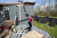 Layla Winbush walks over the debris of her family's destroyed auto detailing business in Lake Charles, La., in the aftermath of Hurricane Laura, Sunday, Aug. 30, 2020. (AP Photo/Gerald Herbert)