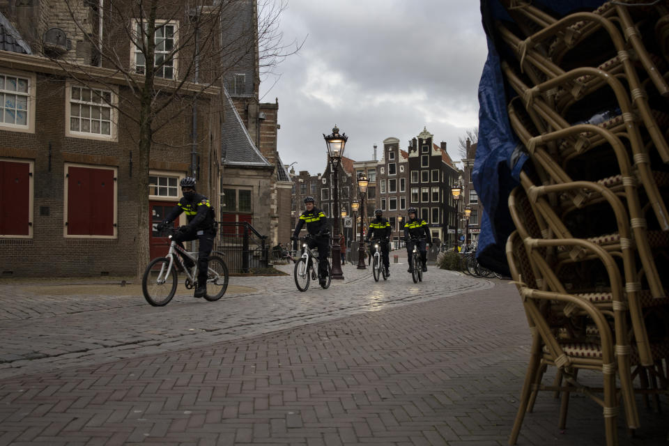 Police officers on bicycles pass stacked up terrace chairs outside a bar in the near-empty Red Light District in Amsterdam, Thursday, Jan. 14, 2021. The Dutch government this week extended by three weeks the tough lockdown in force since mid-December amid fears that coronavirus infection rates are not declining quickly enough and fears about a new more transmissible variant of the COVID-19 virus. (AP Photo/Peter Dejong)