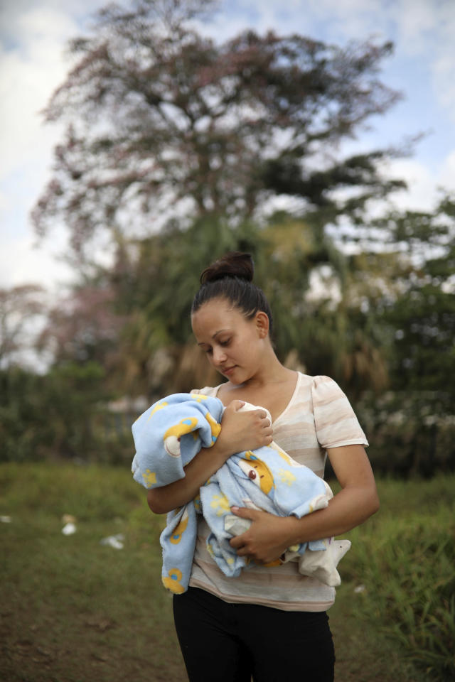 <p>Honduran migrant Genesis Martinez, 18, poses for a picture holding her two-month-old son Cesar at the sports club where they have been camping out, in Matias Romero, Oaxaca State, Mexico, Thursday, April 5, 2018. Martinez decided to join the migrant caravan after the woman she had been working for near Mexico's southern border threw her out of the house after she gave birth.(Photo: Felix Marquez/AP) </p>