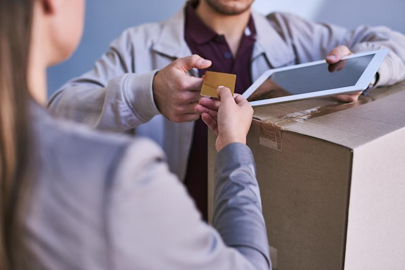 Cropped shot of a courier accepting a credit card payment for a delivery