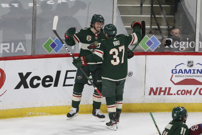 Minnesota Wild's Kyle Rau (37) celebrates with Luke Johnson (41) after Johnson scored a goal against the Colorado Avalanche during the first period of an NHL hockey game Wednesday, April 7, 2021, in St. Paul, Minn. (AP Photo/Stacy Bengs)