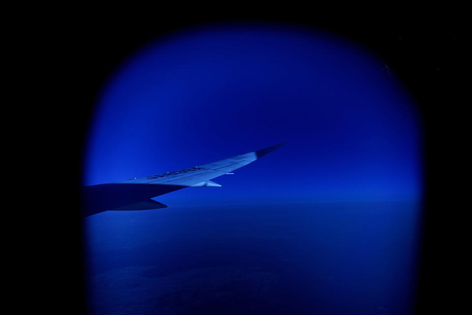 A wing of a plane is seen through a window on a flight Monday, July 19, 2021, from Frankfurt, Germany to Tokyo ahead of the 2020 Summer Olympics. (AP Photo/Natacha Pisarenko)