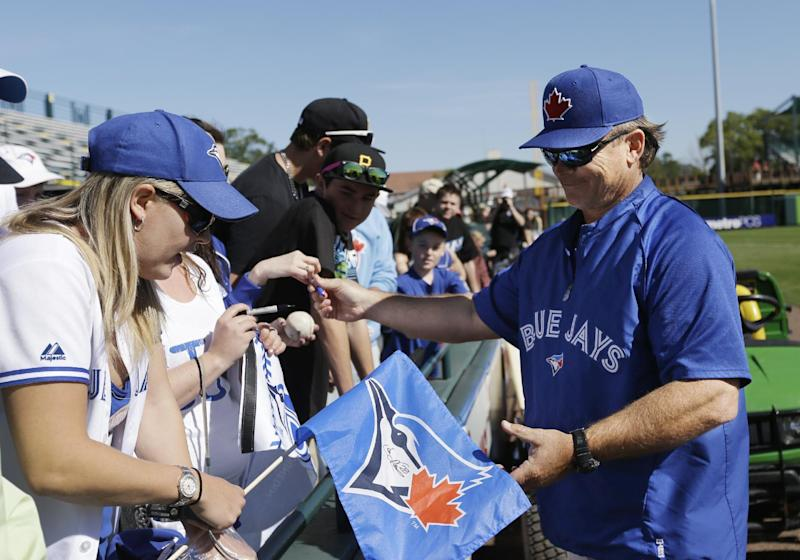 Toronto Blue Jays manager John Gibbons signs autographs before an exhibition spring training baseball game against the Pittsburgh Pirates, Wednesday, March 13, 2013 in Bradenton, Fla. (AP Photo/Carlos Osorio)
