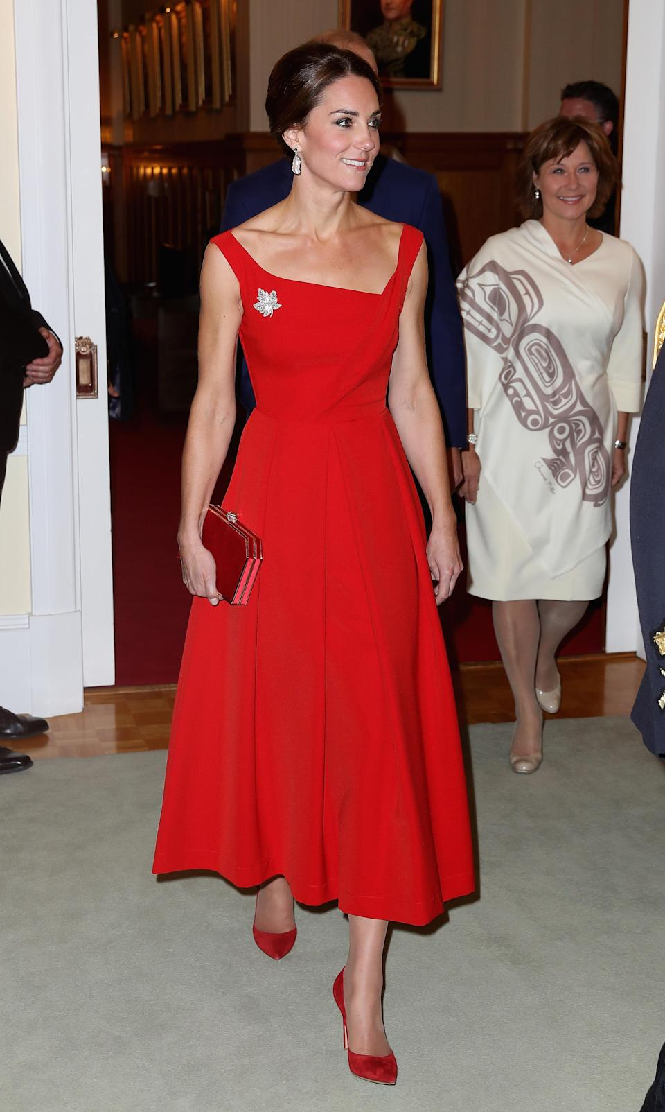 <p>The Duchess dressed diplomatically for an evening reception in Canada thanks to a red Preen dress accessorised with a maple leaf brooch. She finished the ensemble with a matching suede clutch and shoes. <em>[Photo: Getty]</em> </p>