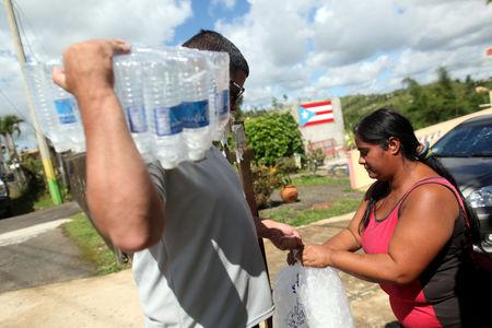 FILE PHOTO: Municipal workers distribute water and ice provided by the U.S. Federal Emergency Management Agency (FEMA), after Hurricane Maria hit the island in September 2017, in Comerio, Puerto Rico January 31, 2018. REUTERS/Alvin Baez
