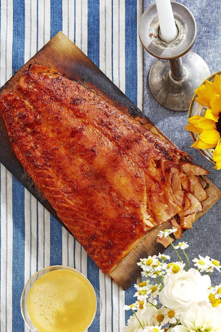 """<p>A cedar plank gives this grilled salmon sweet and savory flavors.</p><p><strong><a href=""""https://www.countryliving.com/food-drinks/a22665225/sweet-and-smoky-cedar-planked-salmon-recipe/"""" rel=""""nofollow noopener"""" target=""""_blank"""" data-ylk=""""slk:Get the recipe"""" class=""""link rapid-noclick-resp"""">Get the recipe</a>.</strong></p><p><strong><a class=""""link rapid-noclick-resp"""" href=""""https://www.amazon.com/Cedar-Grilling-Planks-12-Pack/dp/B009BFBNWO?tag=syn-yahoo-20&ascsubtag=%5Bartid%7C10050.g.1115%5Bsrc%7Cyahoo-us"""" rel=""""nofollow noopener"""" target=""""_blank"""" data-ylk=""""slk:SHOP CEDAR PLANKS"""">SHOP CEDAR PLANKS</a><br></strong></p>"""