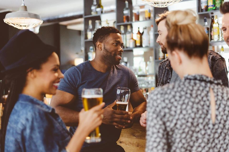 group of happy friends meeting in a pub, standing by the bar counter talking and drinking beer