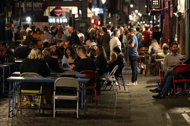 Young people outside the Blue Posts pub in Berwick Street, Soho, London. People in England will be banned from meeting in groups of more than six from Monday as ministers try to tackle the rising number of coronavirus cases across the UK.