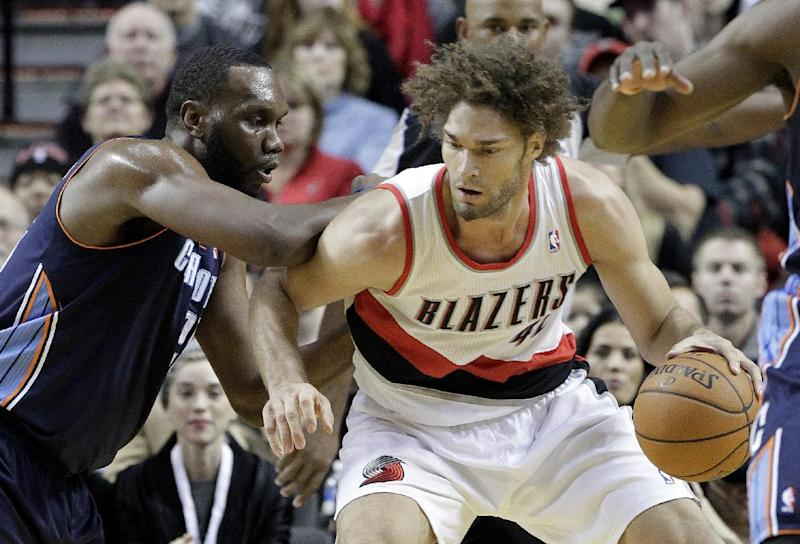 Portland Trails Blazers center Robin Lopez, right, works the ball in against Charlotte Bobcats center Al Jefferson during the first half of an NBA basketball game in Portland, Ore., Thursday, Jan. 2, 2014. (AP Photo/Don Ryan)