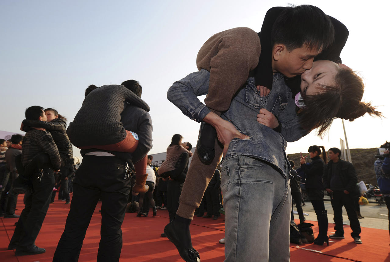 Couples participate in a kissing contest in Hefei, Anhui province February 18, 2012. A total of 63 couples took part in the contest in which men must carry their partners while kissing and try to last as long as possible. The winner will be rewarded a 1-carat diamond ring, local media reported.