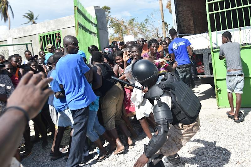 A Haitian policeman pushes back Hurricane Matthew victims waiting for the delivery of food from the UN's World Food Programme in Tobeck, in Les Cayes, in the south west of Haiti on October 13, 2016