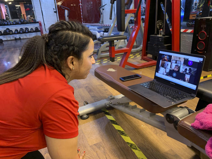 Kanika Gautam, owner of the Ultra Bodies Fitness Studio, takes online class from their closed Gyms on the outskirts of New Delhi, India, Thursday, June 10, 2021. Gyms were among the last types of venues allowed to reopen from the 2020 lockdown and they were closed again during the latest outbreaks. The Gautams had been thriving on income from their 100 gym members, making enough to rent their two-story space and pay five trainers. Now, they're relying on whatever they can scrape together from offering online fitness training, and struggling to afford rent and school fees for their two children. (AP Photo/Rishabh R. Jain)