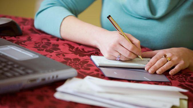 woman writing a check in her checkbook