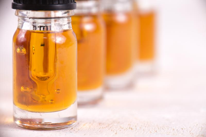 Four vials of cannabidiol oil lined up on a counter.