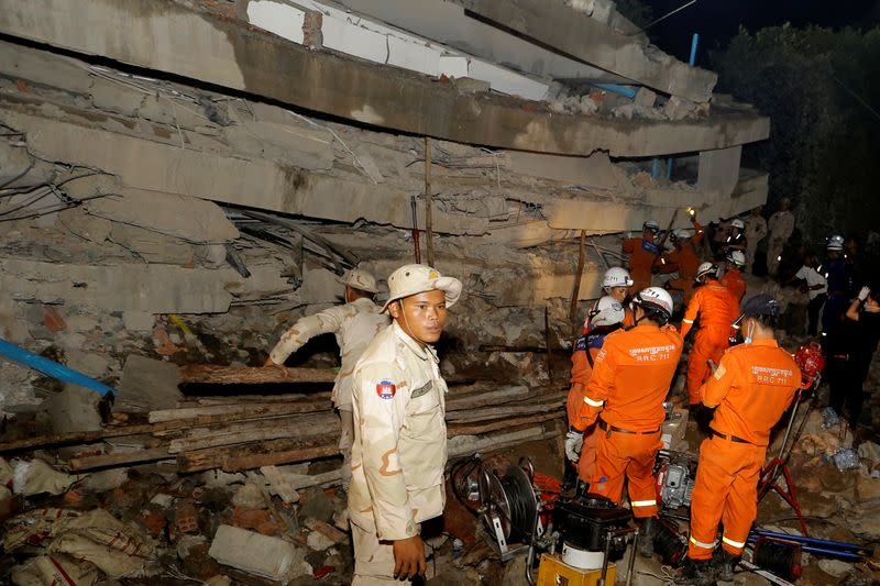 A rescue team searches for trapped workers at a collapsed building, which was under construction in Kep, Cambodia
