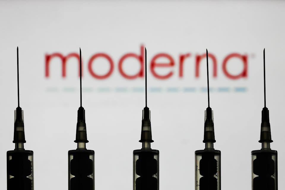 Medical syringes are seen with Moderna company logo displayed on a screen in the background in this illustration photo taken in Poland on October 12, 2020. (Photo illustration by Jakub Porzycki/NurPhoto via Getty Images)