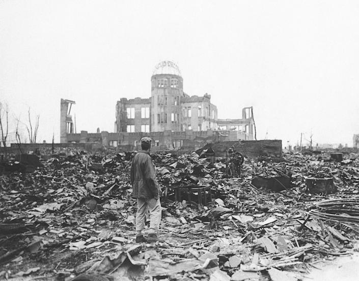 FILE - In this 1945 file photo, an Allied war correspondent stands in the ruins of Hiroshima, Japan, just weeks after the city was leveled by an atomic bomb. Many residents of Hiroshima welcome attention to their city from abroad, which IOC President Thomas Bach will bring when he visits on Friday, July 16. But Bach will also bring political baggage — as will his vice president John Coates when he visits Nagasaki the same day — that is largely unwelcome in two cities viewed as sacred by many Japanese. (AP Photo/File)