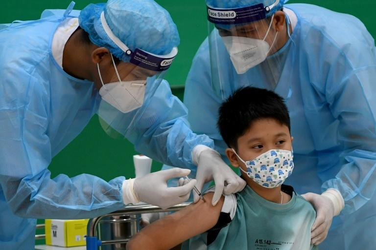 Prime Minister Hun Sen's grandson receives a Sinovac dose as Cambodia rolls out jabs for under 12s (AFP/TANG CHHIN Sothy)