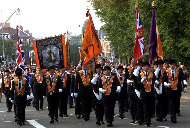 FILE PHOTO: Members of the Ballynafeigh Orange Lodge march away from the security barrier on the Ormeau Road, Belfast