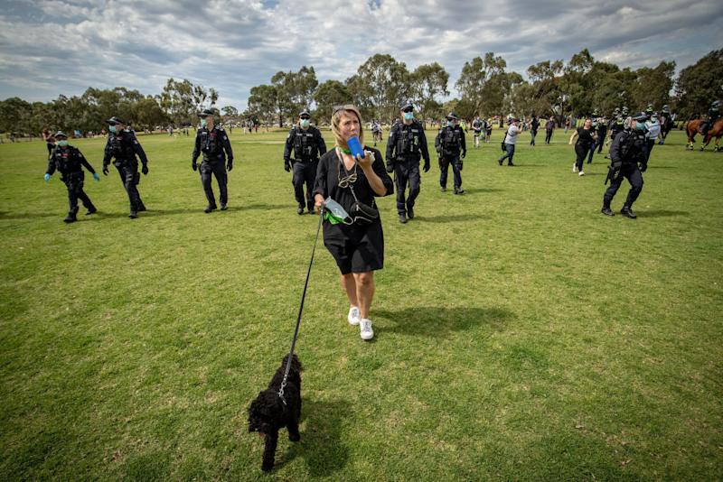 Woman walks her dog while wearing a mask as a group of police officers walk behind her in Melbourne. Source: Getty