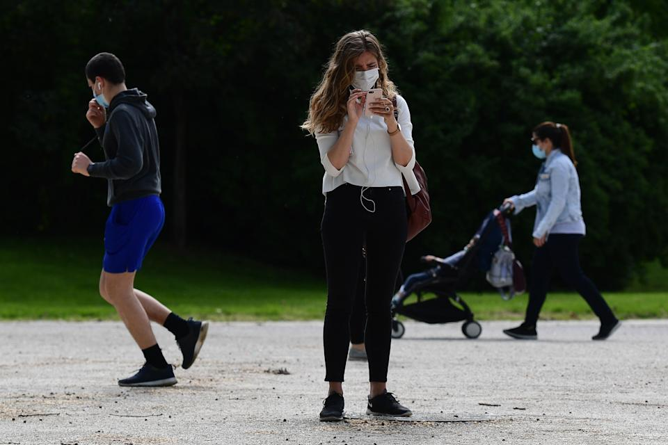 A woman checks her smartphone in the Parco Sempione park on May 4, 2020 in Milan as Italy starts to ease its lockdown, during the country's lockdown aimed at curbing the spread of the COVID-19 infection, caused by the novel coronavirus. - Stir-crazy Italians will be free to stroll and visit relatives for the first time in nine weeks on May 4, 2020 as Europe's hardest-hit country eases back the world's longest nationwide coronavirus lockdown. (Photo by Miguel MEDINA / AFP) (Photo by MIGUEL MEDINA/AFP via Getty Images)