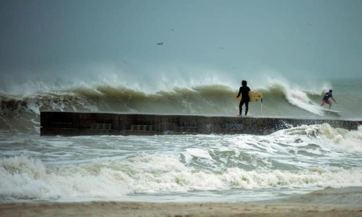 A surfer times the waves before jumping off the jetty into the surf before the arrival of Tropical Storm Eta in Florida