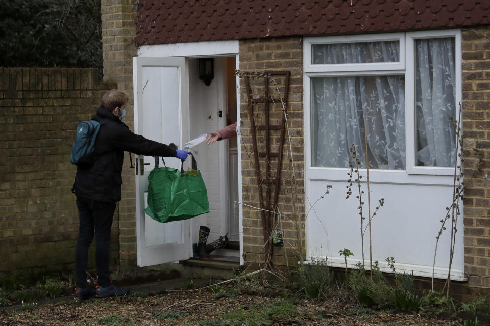A resident throws their household's completed COVID-19 home testing kits that they received earlier in the day, to a volunteer going door-to-door in Woking, England, Tuesday, Feb. 2, 2021, during England's third national lockdown since the coronavirus outbreak began. British health authorities plan to test tens of thousands of people in a handful of areas of England in an attempt to stop a new variant of the coronavirus first identified in South Africa spreading in the community. The Department of Health says a small number of people in England who had not travelled abroad have tested positive for the strain. (AP Photo/Matt Dunham)