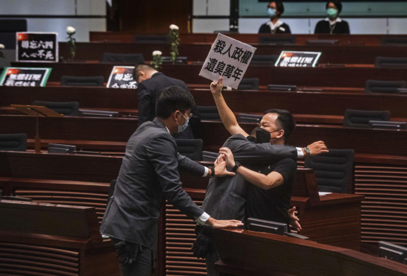"""Pan-democratic legislator Chan Chi-chuen holding a placard reading """"A murderous regime stinks for ten thousand years"""" scuffles with security guards at the main chamber of the Legislative Council dropping a pot of a pungent liquid in the chamber in Hong Kong, Thursday, June 4, 2020. A Hong Kong legislative debate was suspended Thursday afternoon ahead of an expected vote on a contentious national anthem bill after pro-democracy lawmakers staged a protest.(AP Photo/Chan Cheuk Fai/Initium)"""