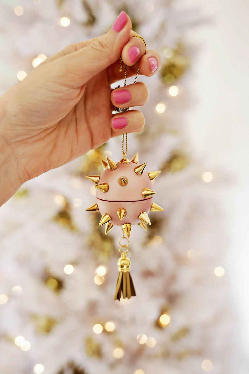 """<p>Here's a fun idea: Assemble DIY ornament kits as Christmas gifts for friends and family members. Tuck everything they need—a circular lip balm, metal studs, a tassel, and some craft glue—into a tiny bakery box with a holiday greeting that includes simple instructions. </p><p><em>Get the tutorial at <a href=""""https://abeautifulmess.com/upcycle-a-lip-balm-into-an-ornament/"""" rel=""""nofollow noopener"""" target=""""_blank"""" data-ylk=""""slk:A Beautiful Mess"""" class=""""link rapid-noclick-resp"""">A Beautiful Mess</a>.</em></p><p><a class=""""link rapid-noclick-resp"""" href=""""https://www.amazon.com/eos-Organic-Lip-Balm-Sphere/dp/B00B6A9KTU/?tag=syn-yahoo-20&ascsubtag=%5Bartid%7C10072.g.34443405%5Bsrc%7Cyahoo-us"""" rel=""""nofollow noopener"""" target=""""_blank"""" data-ylk=""""slk:SHOP LIP BALM"""">SHOP LIP BALM</a></p>"""