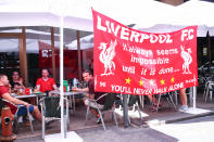 Liverpool fans enjoying a drink next to a banner before the UEFA Champions League final. (Photo by Robbie Jay Barratt - AMA/Getty Images)