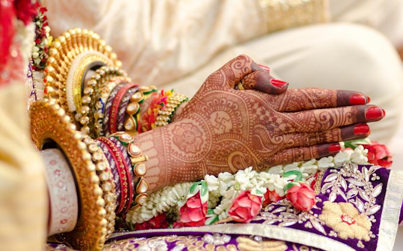 Traditional bridal jewelry and henna decoration on the hands of the bride during a religious ceremony at a Hindu wedding in Jaipur - mahesh hariani
