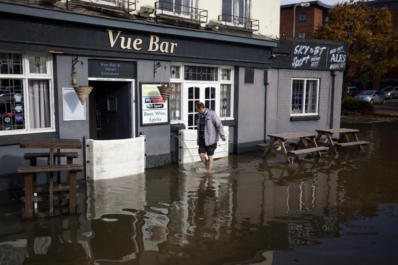 A staff member walks outside the flooded Vue Bar in Worcester, after Britain has been hit by widespread flooding after rivers burst their banks following the weekend's heavy rain, Monday, Oct. 28, 2019. (Jacob King/PA via AP)