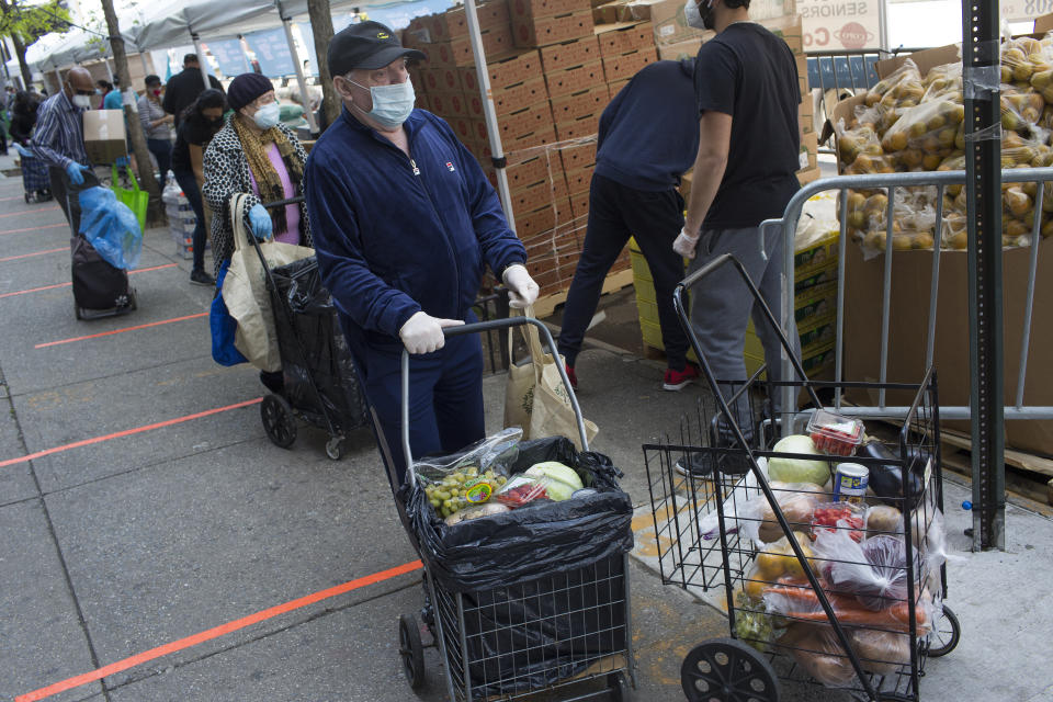 BROOKLYN, NY - MAY 15: A long line forms to receive free food from a food pantry run by the Council of Peoples Organization on May 15, 2020 in the Midwood neighborhood of Brooklyn, New York. As unemployment claims continue to increase in New York City, the lines for free food continue to grow. (Photo by Andrew Lichtenstein/Corbis via Getty Images)