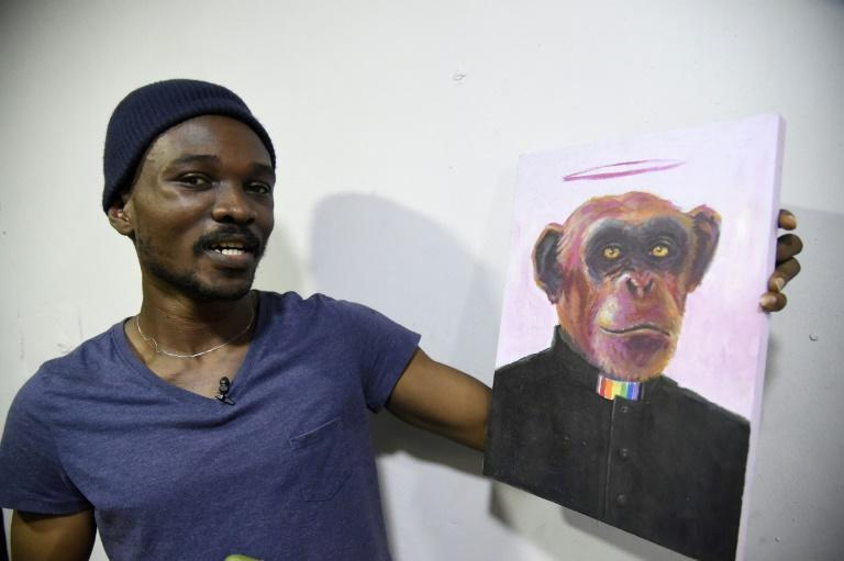 Agbaje at his studio, holding a painting 'Rain Priest'