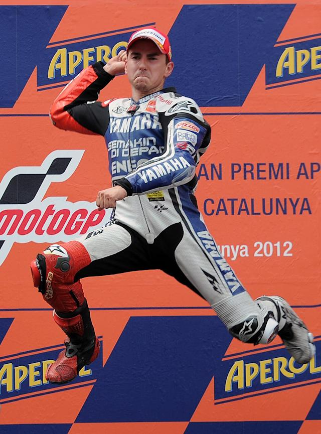 Yamaha Factory Racing's Spanish Jorge Lorenzo celebrates on the podium after winning the MotoGP race of the Catalunya Moto GP Grand Prix at the Catalunya racetrack in Montmelo, near Barcelona, on June 3, 2012. Yamaha Factory Racing's Spanish Jorge Lorenzo won the race ahead of Repsol Honda Team's Spanish Dani Pedrosa and Repsol Honda team's Italian Andrea Dovizioso. AFP PHOTO / LLUIS GENELLUIS GENE/AFP/GettyImages