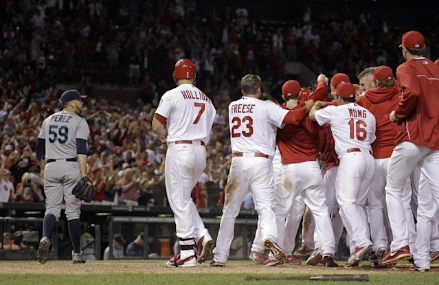 Seattle Mariners relief pitcher Oliver Perez, left, walks off the field as St. Louis Cardinals congratulate Pete Kozma after Kozma scored the game-winning run on a passed ball during the 10th inning of a baseball game Friday, Sept. 13, 2013, in St. Louis. The Cardinals won 2-1. (AP Photo/Jeff Roberson)