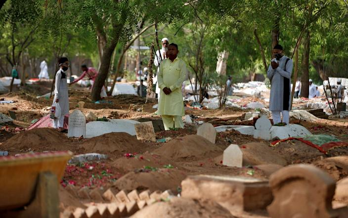 Muslims pray next to the graves of Covid-19 victims in Ahmedabad, India - Reuters