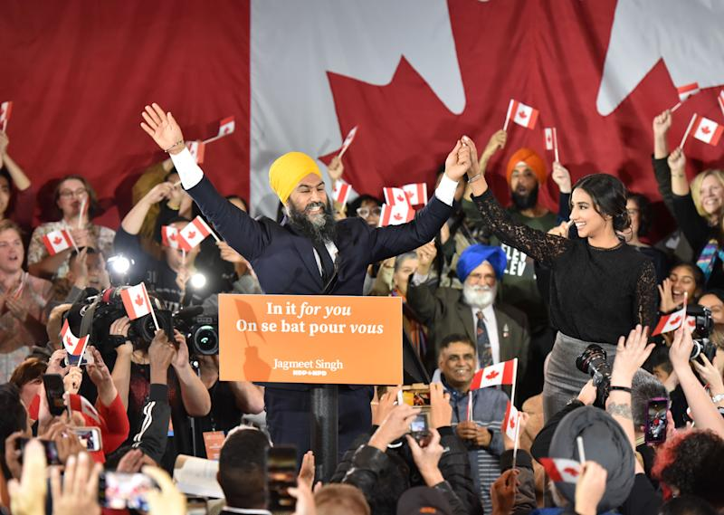 TOPSHOT - NDP leader Jagmeet Singh and his wife Gurkiran Kaur step on stage under the cheers of his supporters at the NDP Election Night Party in Burnaby BC, Canada, on October 21, 2019. - Prime Minister Justin Trudeau's Liberal Party held onto power in a nail-biter of a Canadian general election on Monday, but as a weakened minority government. Television projections declared the Liberals winners or leading in 157 of the nation's 338 electoral districts, versus 121 for his main rival Andrew Scheer and the Conservatives, after polling stations across six time zones closed. NDP Leader Jagmeet Singh failed to gain seats for the party. (Photo by Don MacKinnon / AFP) (Photo by DON MACKINNON/AFP via Getty Images)