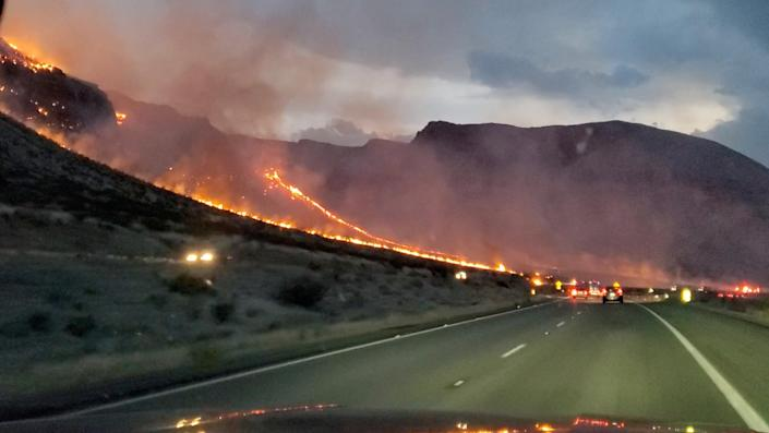 Flames are seen on side of the highway after a bushfire broke out, near St. George, Arizona on 12 July 2021, in this still image obtained from a social media video (Reuters)