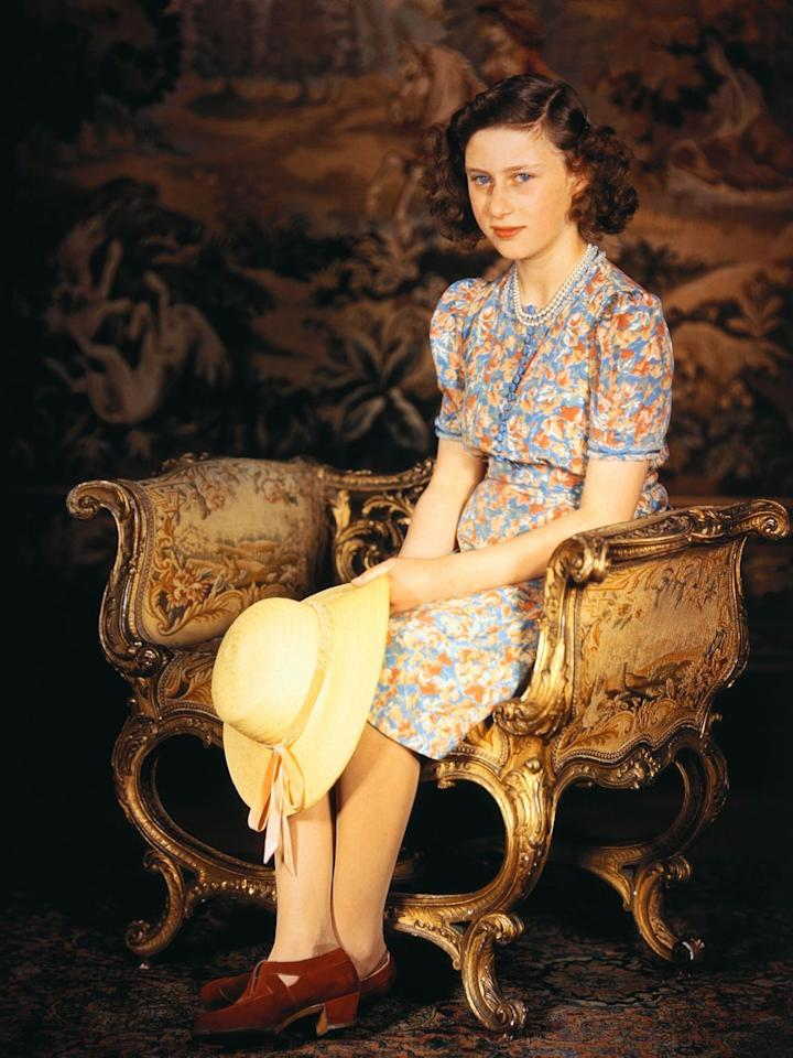 <p>Princess Margaret, seated and wearing a multi-colored dress and holding a straw hat.</p>